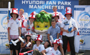 English football fans pose with Zakumi, at Hyundai Fan Park Photo Zone in Manchester, England